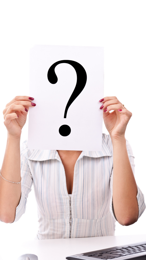woman holding paper with question mark